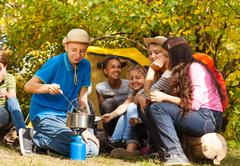 Boy cooking soup in pot for friends at  campsite - stock photo