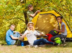 Teenagers build yellow tent during autumn day Stock Photos