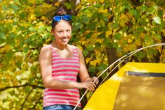 Asian girl build yellow tent herself during day - stock photo