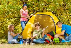 Teenagers build yellow tent themselves in forest Stock Photos