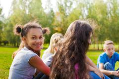 Happy international teens sit together on meadow - stock photo