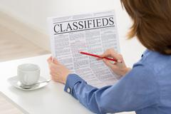 Stock Photo of Close-up Of Businesswoman Highlighting Advertisement On Newspaper