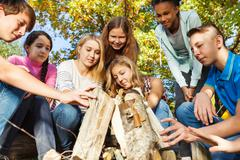 International teens construct bonfire together Stock Photos