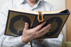 An old man hands holding the Koran - stock photo