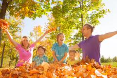 Family throwing leaves in the air during play - stock photo