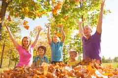 Family playing and throwing leaves in the air - stock photo