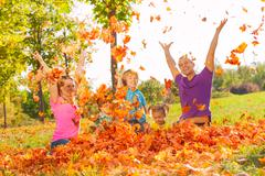 Family playing with leaves and throwing them Stock Photos