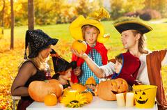 Family in costumes with Jack-O'-Lantern pumpkin - stock photo
