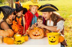 Family craft together Jack-O'-Lantern from pumpkin - stock photo