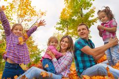 Family with three girls in autumn leaves - stock photo