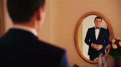 Handsome groom looks on reflection in the mirror and corrects the bowtie Stock Footage