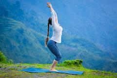 Woman doing yoga asana Utkatasana outdoors Stock Photos