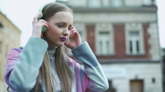 Pretty girl taking mint headphones of the head and looking around, steadycam sho Stock Footage