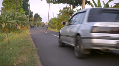 A two lane paved road with a couple of motorcycles and a car driving by. - stock footage