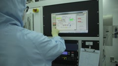Man in a clean room suit operating a Touch screen Stock Footage