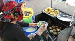Woman makes Banh khot mini savory coconut pancake Stock Footage