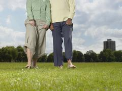 Elderly couple walking bare foot in the park Stock Photos