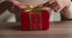 A woman is tying gold ribbon on red gift box - stock footage
