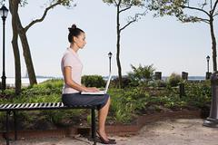 Woman telecommuting in a park - stock photo