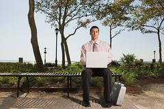 Man telecommuting in a park - stock photo