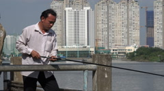 A man is fishing in front of modern apartment blocks in Saigon, HCMC, Vietnam Stock Footage