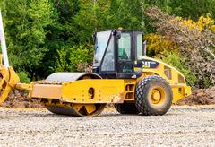 Heavy bulldozer loading and moving gravel on road construction site Stock Photos