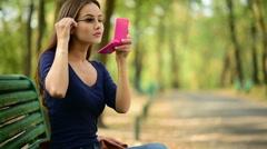 Young beautiful woman makes makeup. Outdoor Stock Footage