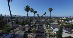 Aerial shot moving down a classic Los Angeles street between the swaying palm tr Stock Footage
