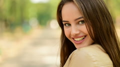 Beautiful young woman closeup against green  park - stock footage