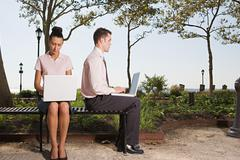 Two people telecommuting in a park - stock photo