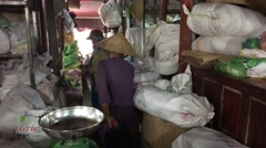 Vietnamese woman walks at an indoor market - stock footage