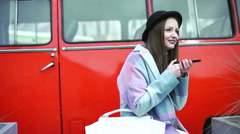 Pretty girl sitting next to the red car and talking on loudspeaker Stock Footage