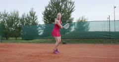 4K Female Tennis Player Hits The Ball With Two Handed Backhand Stroke - stock footage