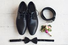 Black bowtie, leather shoes, belt, flower boutonniere on white wood background Stock Photos