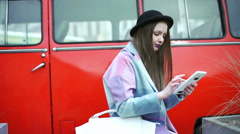Stock Video Footage of Girl in pastel jacket sitting next to the red bus and browsing internet on table