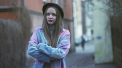 Pretty girl in bright clothes looking unhappy and standing in the alley, steadyc Stock Footage