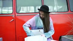 Pretty girl in pastel jacket sitting on the square and looking for something in  Stock Footage