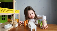 A cute girl playing with a dollhouse Stock Footage