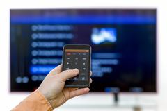 Hand holding smartphone using app with remote control - stock photo