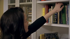 Woman pulls a book off the bookshelf - stock footage