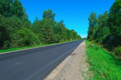 Empty highway with green forest on both sides Stock Photos