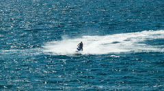 Man Riding Jet Ski Speeding on Blue Ocean Water with White Splashes Stock Footage