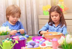 Brother and sister coloring Easter eggs Stock Photos