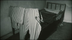 The iron bed from the prison cell with clothes Stock Footage
