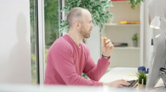 4K Portrait of casual businessman eating snacks at his desk in creative office Stock Footage