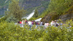 People Walking Along Path with Nugget Falls Background at Mendenhall Glacier Stock Footage