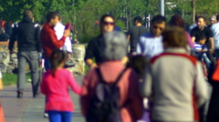 Generic people wander around aimlessly like shadows. Anonymous crowd of people - stock footage