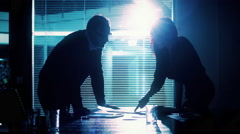 Male and female silhouettes in a meeting room during work Stock Footage