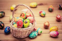 Stock Photo of Colorful hand painted Easter eggs in basket and on wood. Traditional decorati