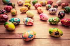 Stock Photo of Colorful hand painted Easter eggs on wood. Unique handmade, vintage design.
